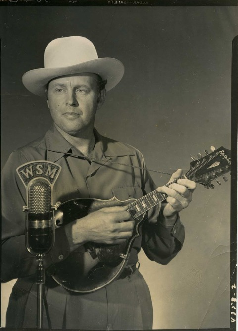 Bill Monroe with Epiphone mandolin posing in front of WSM mic.